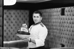 Ståendekock som framlägger en maträtt på hotellrestaurangen som ångar en maträtt med svartvita signaler för ett räkningslock royaltyfria foton