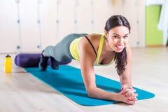 Ståendekondition som utbildar den idrotts- sportiga kvinnan som gör plankaövning i idrottshall- eller yogagruppbegreppet som övar Fotografering för Bildbyråer
