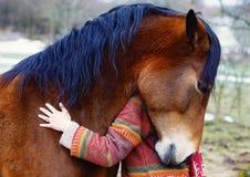 Ståendekvinna och häst i utomhus- Kvinna som kramar en häst Arkivfoto