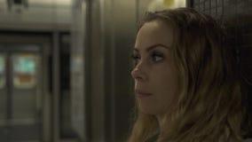 Ståendekvinna på det väntande drevet för gångtunnelstation på plattformen Ung kvinna för handelsresande i tunnelbana Stadstranspo arkivfilmer