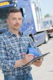 Ståendelastbilchaufför med skrivplattan arkivbilder
