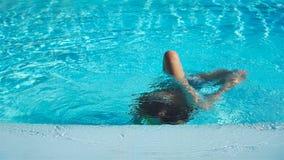 Ståendeliten flicka som har gyckel i utomhus- simbassäng arkivfilmer