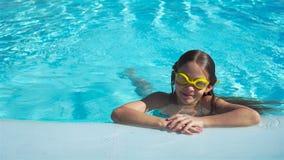 Ståendeliten flicka som har gyckel i utomhus- simbassäng Unge som tycker om semester stock video
