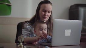 St?endemoder och liten son som inomhus placeras med en b?rbar dator p? tabellen Upptagen ung moder som hemma arbetar Barnet stock video