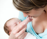 Ståendemoderholdingen behandla som ett barn flickan i henne armar Royaltyfri Foto