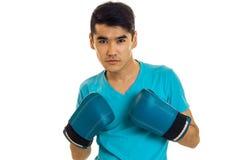 Ståenden av allvarliga brunettsportar man den praktiserande asken i blåa handskar som isoleras på vit bakgrund Royaltyfri Foto