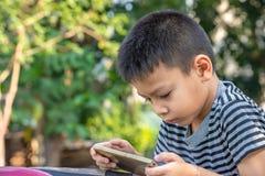 Ståenden av asiatiska pojkar spelar mobiltelefoner parkerar in royaltyfria foton