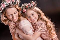 Ståenden av att krama dottern och modern i blommor virvlar royaltyfri bild