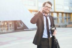 Ståenden av att le affärsmannen som använder smartphonen nära kontorsbyggande med thermo kaffe, rånar i hand royaltyfri bild