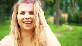 Ståenden av att le den blonda flickan med Holi målar på hennes framsida och hår arkivfilmer