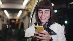 Ståenden av att le den härliga unga kvinnan i hörlurar som offentligt rider transport, lyssnar musik och bläddra på guling lager videofilmer
