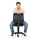 Ståenden av att le den lyckliga manen sitter på kontorsstol arkivbild