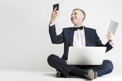Ståenden av att le den stiliga Caucasian mannen i dräkten som använder Digital, betyder arkivfoto