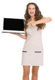 Stående av att le den unga kvinnan som pekar på bärbar dator Arkivbild