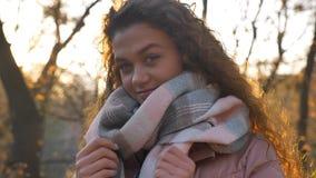 Ståenden av att le denhaired caucasian flickan som rymmer hennes halsduk och håller ögonen på in i kamera i höstligt, parkerar royaltyfria bilder