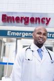 Ståenden av att le doktorn förutom sjukhuset, akutmottagning undertecknar in bakgrunden Arkivbilder