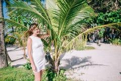 Ståenden av att le härliga kvinnor som bär den vita klänningen nära den trevliga gräsplanen, gömma i handflatan tjänstledigheter Royaltyfria Foton