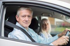 Ståenden av att le höga par på bilen reser tillsammans royaltyfria bilder