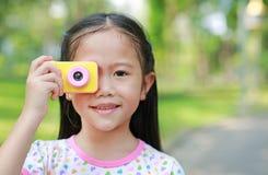 Ståenden av att le lilla flickan tar fotoet med leksaken för den digitala kameran i den utomhus- trädgården arkivfoton