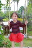 Ståenden av att le liten asiatisk barnflickalek och att sitta på gungan i naturen parkerar royaltyfri foto
