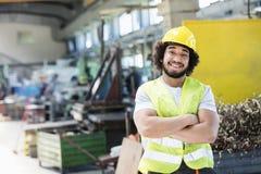 Ståenden av att le manliga anseendearmar för den manuella arbetaren korsade i metallbransch royaltyfri bild