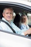 Ståenden av att le mogna par på bilen reser tillsammans fotografering för bildbyråer