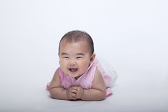 Ståenden av att le och att skratta behandla som ett barn att ligga ner, studioskottet, vit bakgrund Arkivbilder