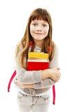 Ståenden av att le skolaflickan med ryggsäckinnehavet bokar royaltyfri foto