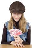 Ståenden av att le unga flickan som spelar kort och ser kameran, är hon mycket nöjd med de vinnande korten i hennes hand Arkivfoto
