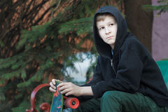 Ståenden av att vila den hållande skateboarden för den tonårs- pojken och sammanträde parkerar på bänken Arkivbilder