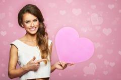 Ståenden av attraktivt le mörkt hår för kvinnan som isolerades på rosa studio, sköt med hjärta lycklig förälskelse Fotografering för Bildbyråer