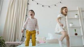 Ståenden av barn som hoppar på en säng-, pys- och flickasyskongrupp, har gyckel och att skratta stock video