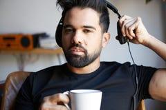 Ståenden av barn uppsökte mannen i hörlurar som lyssnar till hemmastadd musik och dricker kaffe Koppla av och vilotid Arkivfoto