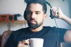 Ståenden av barn uppsökte mannen i hörlurar som lyssnar till hemmastadd musik och dricker kaffe Koppla av och vilotid Arkivbilder