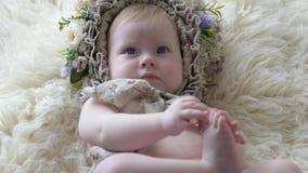 Ståenden av barnet i beslag med blommor ligger på filten och poserar på kameran på photoshoot arkivfilmer