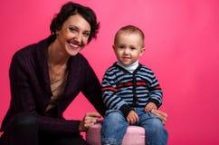 Ståenden av behandla som ett barn och hans moder på en rosa bakgrund arkivbild