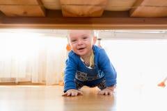 Ståenden av behandla som ett barn pojkekrypning och att se under sängen Royaltyfria Foton