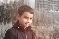 Ståenden av behandla som ett barn pojken i mörkt omslag på hög akromatisk gräsbakgrund arkivbild