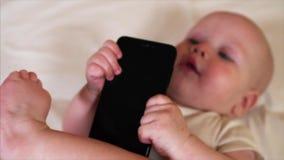 Ståenden av behandla som ett barn pojken som tuggar och den sugande svarta smartphonen lager videofilmer
