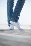 Ståenden av ben med jeans och vit skor utomhus arkivfoto