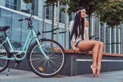 Ståenden av blus och kortslutningar för sexig hippie en kvinnlig bärande i en huvudbindel, sitter barfota på en bänk nära stadscy Royaltyfria Bilder