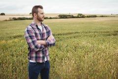 Ståenden av bondeanseendet med armar korsade i fältet royaltyfri foto