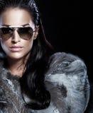 Ståenden av brunettkvinnan som ha på sig solglasögon, och härligt pälsfodrar Arkivbild