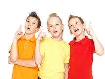 Ståenden av de lyckliga barnen pekar vid fingrar upp - isolerat på Arkivbild