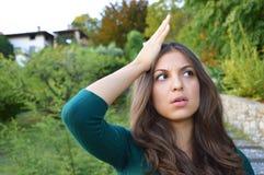 Ståenden av den älskvärda brunettkvinnan mindes något och rymmer en hand arkivfoton