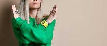 Ståenden av den allvarliga, olyckliga säkra blonda kvinnan som rymmer två armar, korsade och att göra en gest inget tecken, royaltyfri foto
