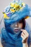 Ståenden av den asiatiska kvinnan med den blom- hatten och blått skyler att se kameran på ljust - grå bakgrund royaltyfria bilder