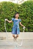 Ståenden av den asiatiska lilla flickan som hoppar det handgjorda repet bland gunga i, parkerar royaltyfria foton