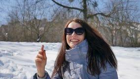 Ståenden av den attraktiva kvinnan i svart solglasögon och rakt spela för mörkt hår kastar snöboll i parkerar utomhus i arkivfilmer