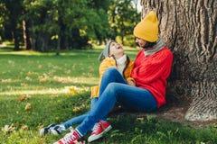 Ståenden av den attraktiva kvinnliga modellen, har angenäm konversation med dottern, vilar på grönt gräs, ser lyckligt, har glädj royaltyfri bild